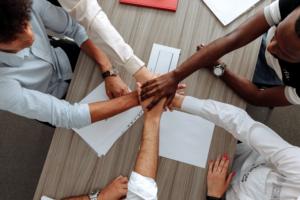 Eine Gruppe von Menschen sitzt um einen Tisch herum und legen die Hände aufeinander.