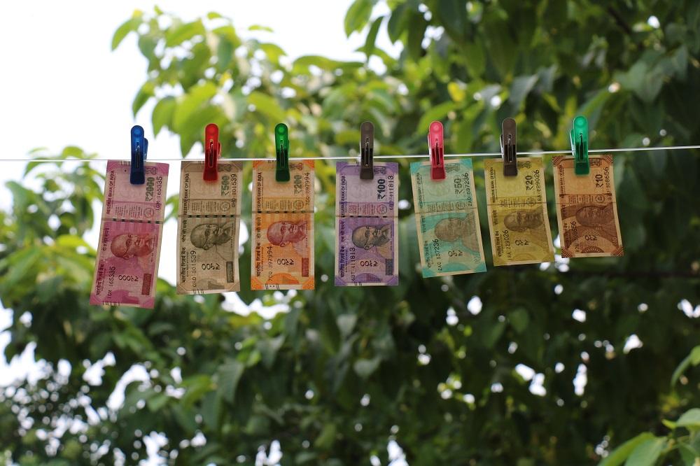 Auf der Wäscheleine sind Geldscheine aufgehängt. Im Hintergrund ist ein Baum.